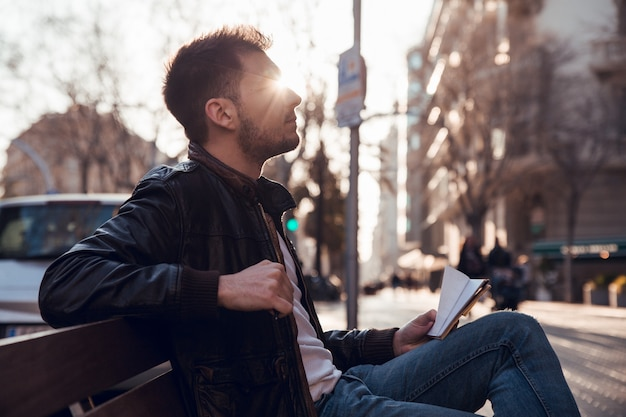 Profile portrait of man with beard at sunset sitting on bench Premium Photo