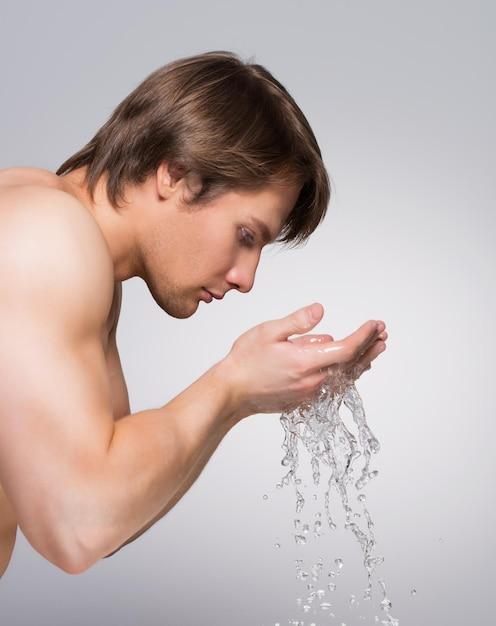 灰色の壁に水で顔を洗うハンサムな男のプロフィールの肖像画。 無料写真