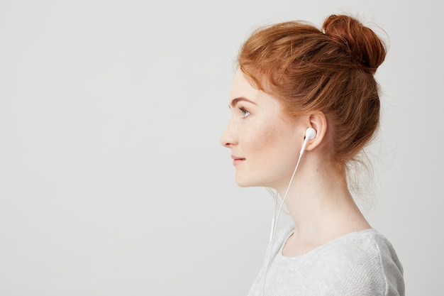 Profile portrait of young beautiful tender redhead girl with bun in headphones smiling . Free Photo