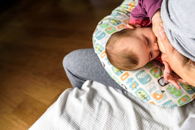 Profile portrait of a young woman breastfeeding a child using a special breastfeeding pillow for newborn babies. Premium Photo