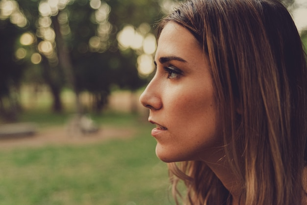 Profile portrait of a young woman looking straight ahead in nature, muted tones and added film grain. Premium Photo