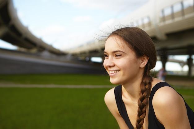 Colpo di profilo di attraente giovane atleta di sesso femminile caucasico con i capelli scuri raccolti in treccia, sorridendo ampiamente, godendo del bel tempo estivo durante l'esercizio all'aperto allo stadio. sport e fitness Foto Gratuite