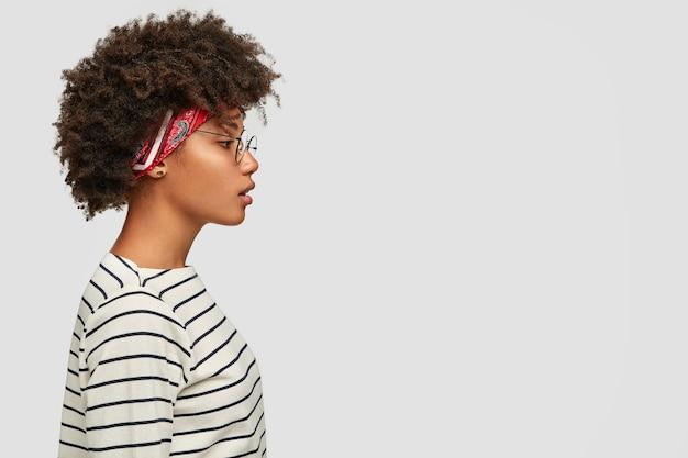 Colpo di profilo di donna nera con taglio di capelli afro, espressione pensosa Foto Gratuite