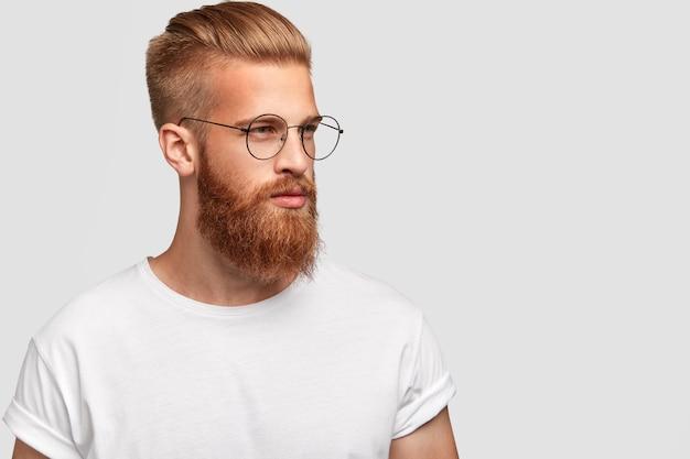 Colpo di profilo di un uomo brutale con una folta barba voluminosa, indossa occhiali rotondi e guarda pensieroso da parte Foto Gratuite