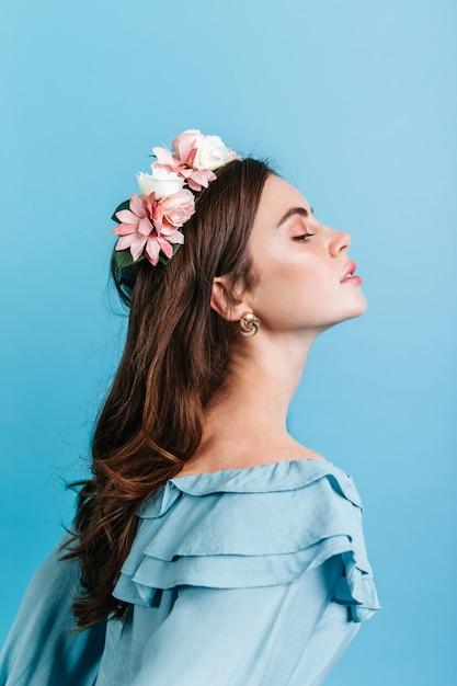 フリル付きブラウスの貴族の女の子のプロフィールショット。青い壁に誇らしげにポーズをとっている彼女の髪に花を持つ女性。 無料写真