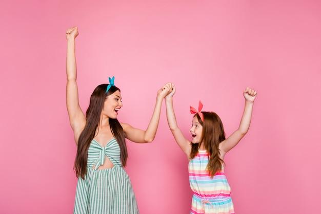 분홍색 배경 위에 절연 밝은 드레스 스커트 머리띠를 입고 비명을 지르는 손을 잡고 흥분된 두 사람의 프로필 측면 사진 프리미엄 사진