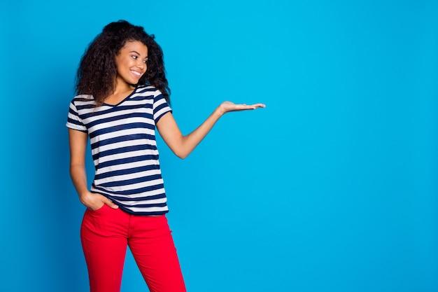 파란색 벽에 뭔가, 제품 프리젠 테이션, 복사 공간을 들고 쾌활한 아프리카 미국 여성 발기인의 프로필 측면보기 프리미엄 사진