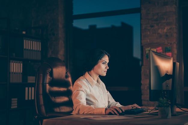 Профиль, вид сбоку, она красивая, привлекательная, целеустремленная, трудолюбивая, топ-менеджер, владелец компании, набирает текст, создает новую сеть архива ит-стартапов в ночное время, в темноте, на рабочем месте, на станции, в помещении Premium Фотографии