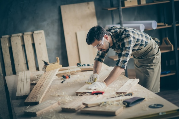 Profile side view portrait of his he nice attractive focused skilled experienced hardworking guy self-employed builder carving wood on table desk at modern industrial loft brick style interior indoors Premium Photo