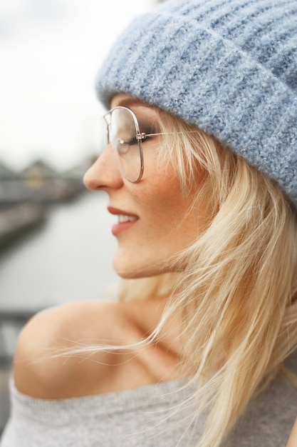 Profile of stunning blonde woman in glasses, blue hat and grey sweater Free Photo