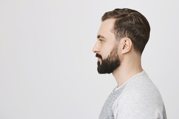 Profile of stylish bearded man made new hairstyle at barber shop Free Photo