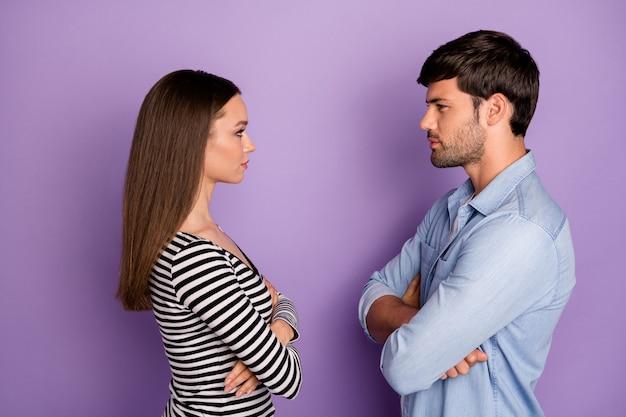 Профиль два человека пара парень дама стоит напротив сердитых глаз, скрестив руки, дралась в стильной повседневной одежде, изолированной пастельно-фиолетовой стене Premium Фотографии