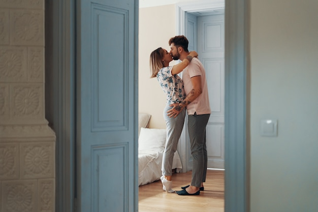 Profile view of loving young couple hugging while standing in their bedroom Premium Photo
