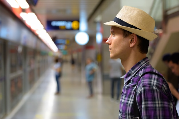 Profile view of young handsome tourist man waiting for train Premium Photo