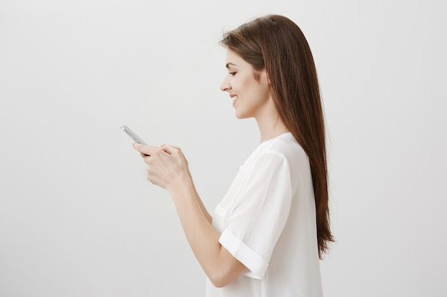 Profile of young pretty woman texting, using mobile phone, order online Free Photo