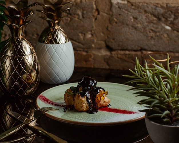 Profiteroles in chocolate sauce inside white plate. Free Photo