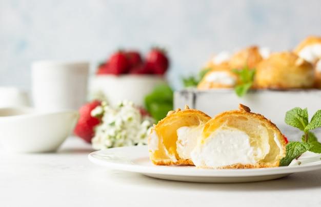 Profiteroles(シューアララクリーム)-カッテージチーズとクリーム、イチゴ、ミント、コーヒーカップを添えたフランスのシューペストリーボール。 Premium写真