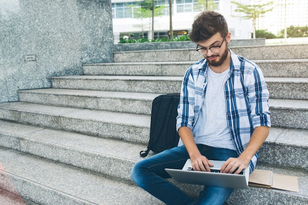 Programmer working on computer on marble stairs in the street Free Photo