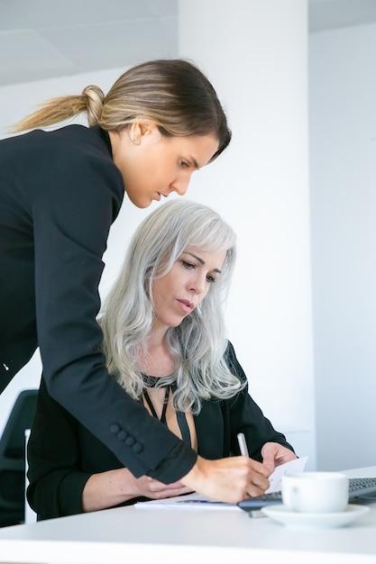 Руководитель проекта стоит рядом с сотрудником, делает заметки в документе или ставит подпись на бумажном отчете. две коллеги-женщины на рабочем месте. концепция делового общения Бесплатные Фотографии