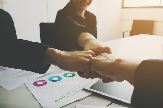 Project team of businessman and businesswoman fist bumping teamwork together. Premium Photo