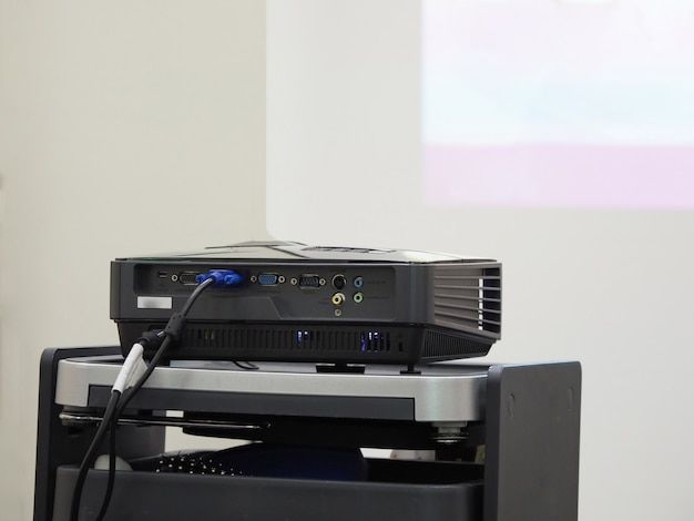 Projector on a black table ready for presentation. Premium Photo
