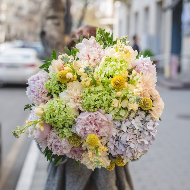 Promoting a mixed flower bouquet in the street. Free Photo