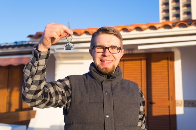 Концепция собственности, владения, нового дома и людей - молодой человек с ключами стоит возле нового дома Premium Фотографии