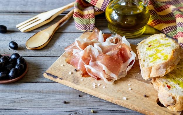 Prosciutto ham and bread on wood Premium Photo