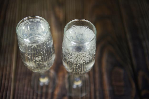 Праздничные напитки из стекла prosecco, такие как тематические вечеринки и праздники с бокалами для шампанского для зимних праздников, украшенные рождеством на деревянном столе Premium Фотографии