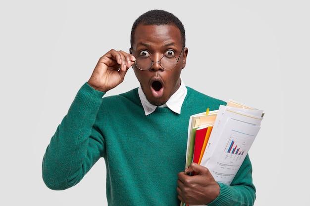 Преуспевающий менеджер по маркетингу-мужчина с удивленным выражением лица, держит за руку очки, несет документы по экономике, изолированные на белом фоне Бесплатные Фотографии