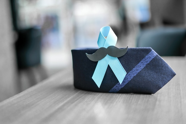 Prostate cancer awareness, light blue ribbon with mustache and necktie Premium Photo