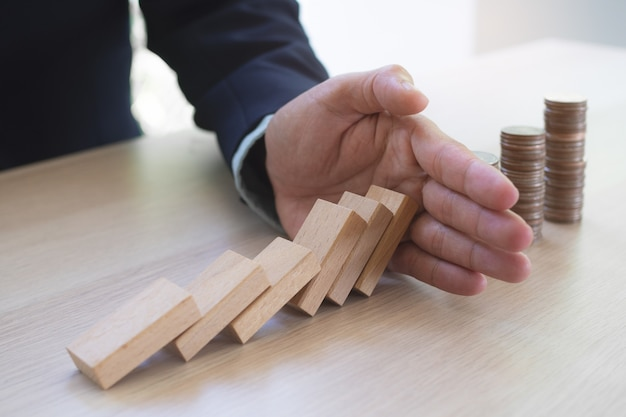 Protection finance from domino effect concept. hands stop domino effect before destroy stack of money. Premium Photo