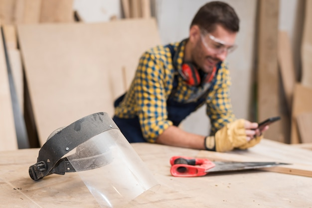 Protective glass mask and handsaw on workbench and carpenter using cellphone at background Free Photo