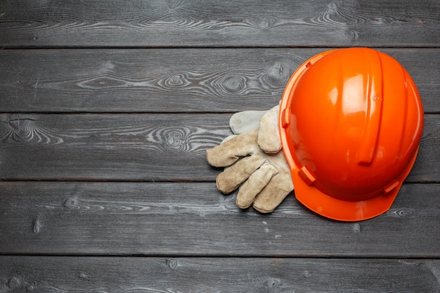 Protective helmet and a pair of working gloves on a wooden surface Premium Photo