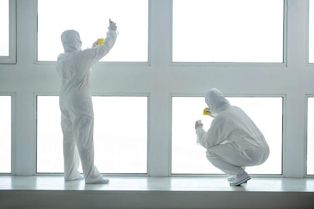 Защитные меры. медицинские работники в защитной одежде и медицинских масках моют и дезинфицируют оконные стекла Premium Фотографии