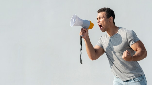 Protester demonstrating with megaphone Free Photo
