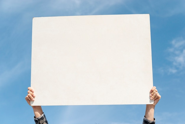 Protester holding board up with mock-up Free Photo