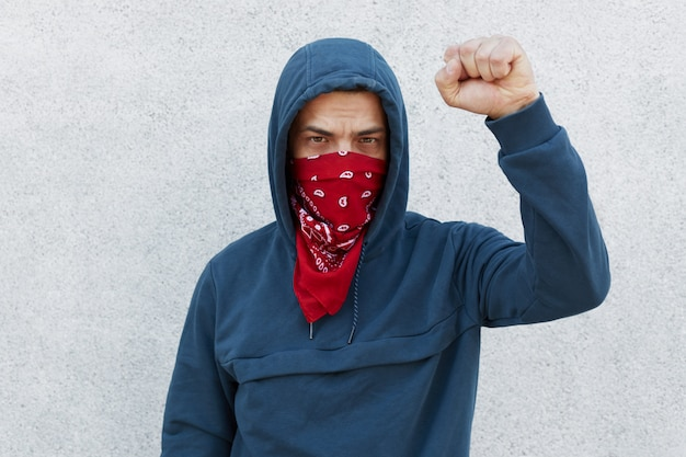 Protester with red bandana mask raises fist Free Photo