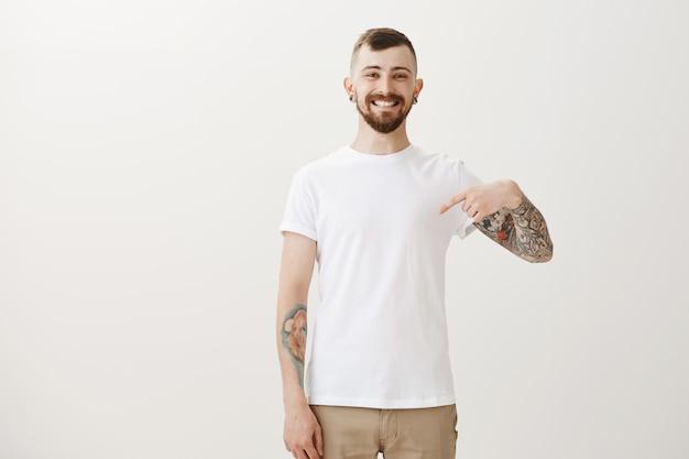 Orgoglioso uomo allegro con tatuaggi rivolti a se stesso e sorridendo soddisfatto Foto Gratuite
