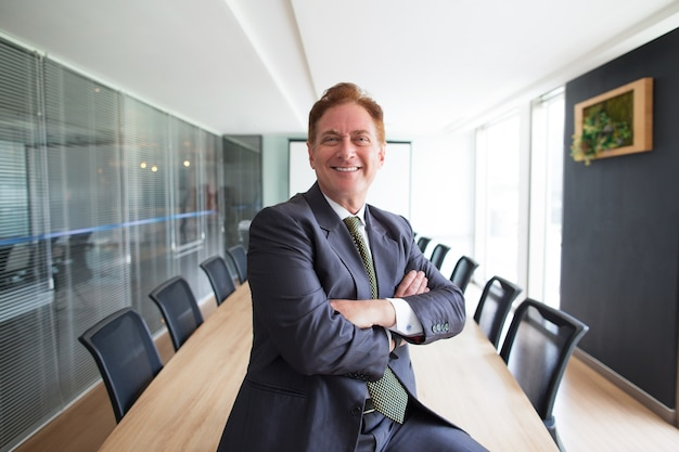 Proud middle-aged business man in conference room Free Photo