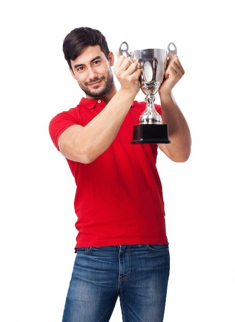 Proud teen holding up the silver cup Free Photo