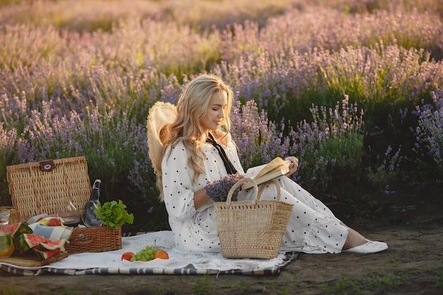 ラベンダー畑でリラックスしたプロヴァンスの女性。ピクニックの女性。麦わら帽子の女性。 無料写真
