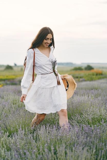 ラベンダー畑でリラックスしたプロヴァンスの女性。白いドレスの女性。 無料写真