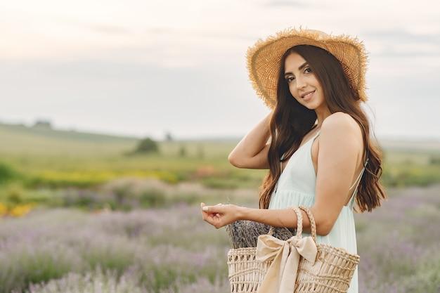 ラベンダー畑でリラックスしたプロヴァンスの女性。麦わら帽子の女性。バッグを持つ少女。 無料写真