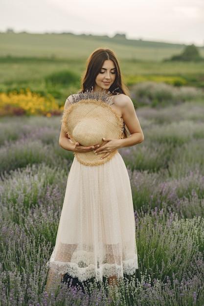 ラベンダー畑でリラックスしたプロヴァンスの女性。麦わら帽子の女性。 無料写真