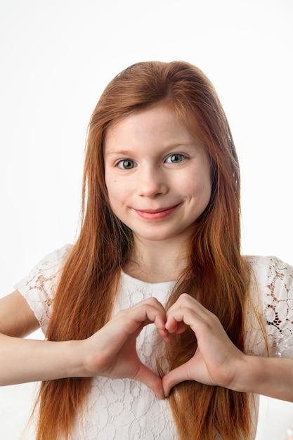 Prtrait улыбается жизнерадостная девушка, делая форму сердца руками на белом фоне. Premium Фотографии