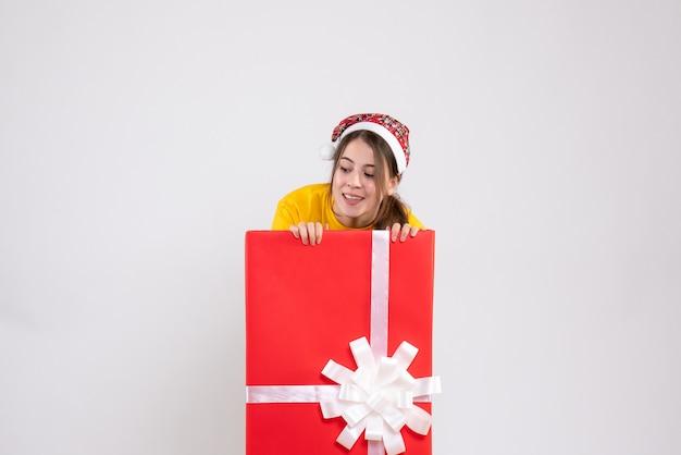 白の大きなクリスマスプレゼントの後ろに立っている何かを見ているサンタ帽子を持つ詮索好きな女の子 無料写真