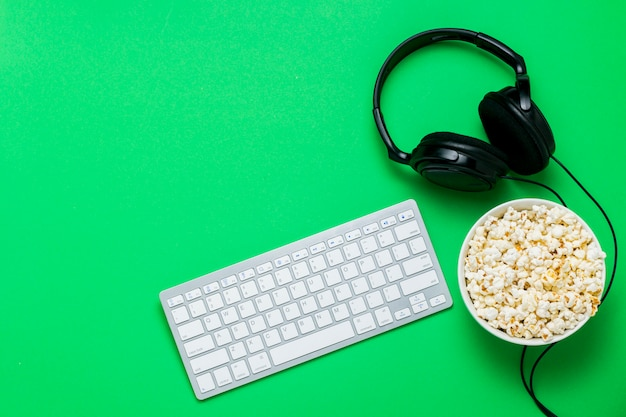 キーボード、ヘッドフォン、緑の背景にポップコーンのボウル。映画、番組、psでのスポーツ、オンラインでのゲームの視聴のコンセプト。フラット横たわっていた、トップビュー。 Premium写真