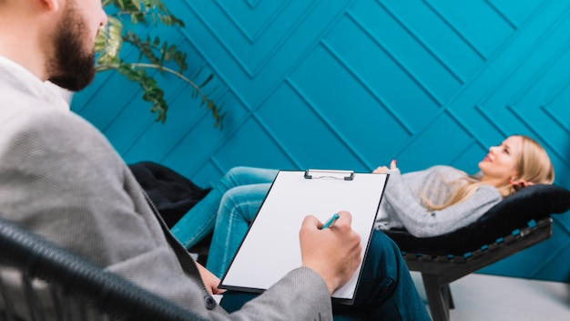 Psychologist listening to her female patient lying on couch and writing down notes Free Photo