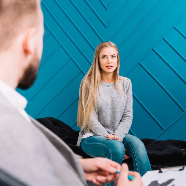 心理学者は彼女の患者に耳を傾け、メモを書き留めて Premium写真